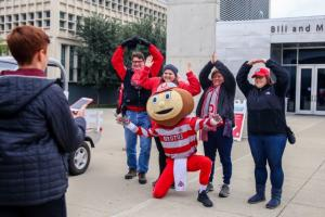 Someone is taking a photo of a family posing for a picture making the OHIO gestures and posing with Brutus, the Ohio State mascot